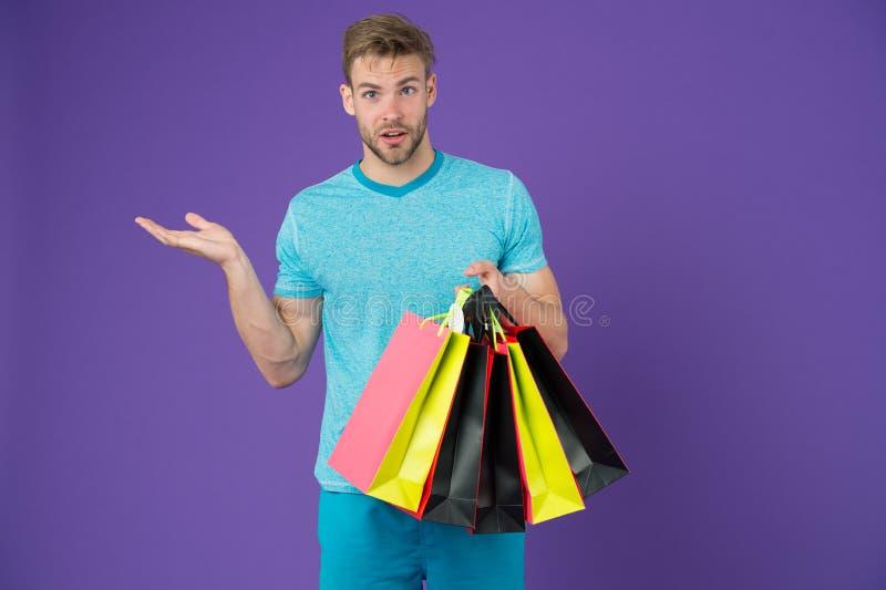 Hombre con los panieres y gesto de mano en el fondo violeta Machista con las bolsas de papel coloridas Comprador de la moda con l imagenes de archivo