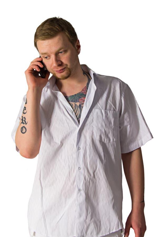 Hombre con los tatuajes que habla sobre el teléfono foto de archivo