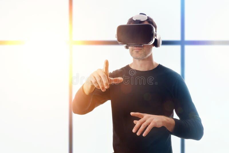 Hombre con los vidrios del vr que señala con su fondo de la ventana del finger imagen de archivo