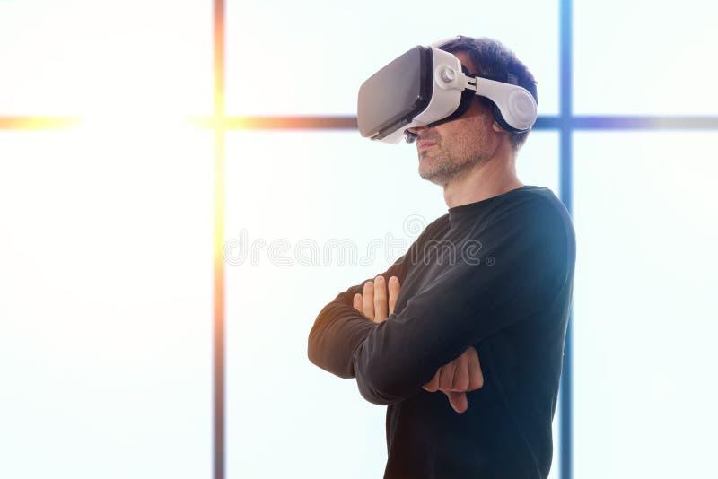 Hombre con los vidrios del vr y las manos y el fondo cruzados de la ventana imágenes de archivo libres de regalías