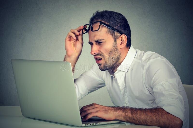 Hombre con los vidrios que tienen problemas de la vista confundidos con software del ordenador portátil imagen de archivo