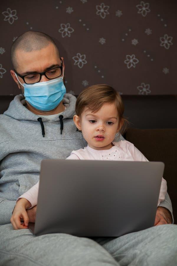 Hombre con máscara protectora con su hija y laptop imagen de archivo