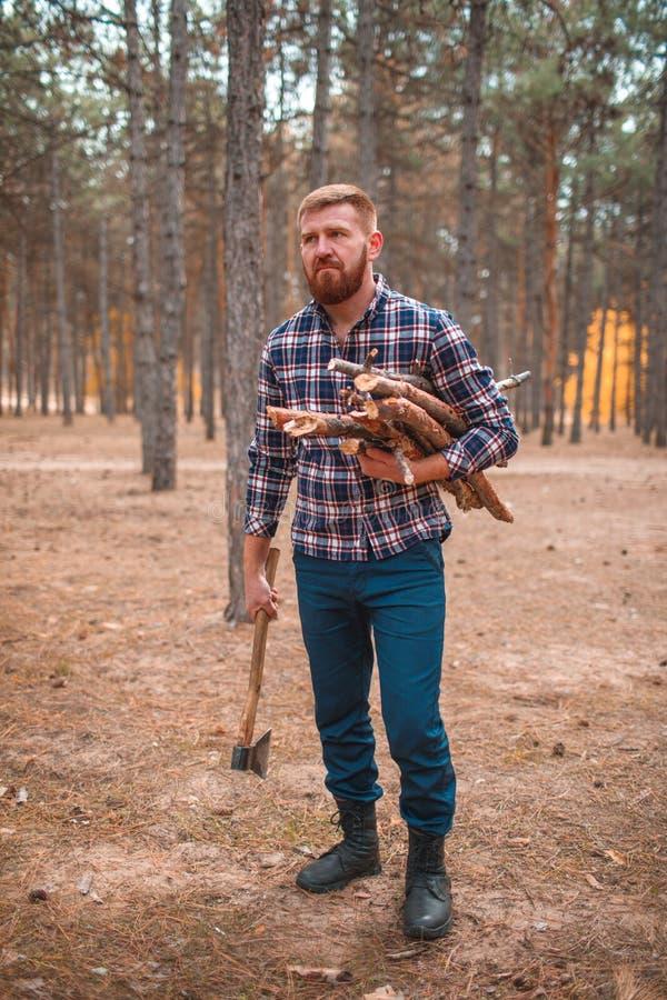 Hombre con madera y un hacha en sus manos en el bosque del otoño imagenes de archivo