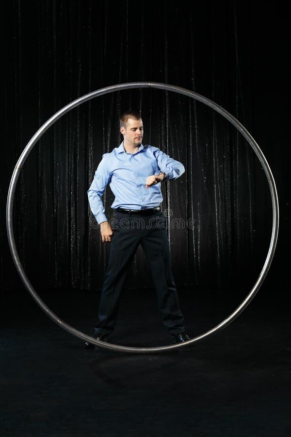 Hombre con mirada del círculo en su reloj en el fondo negro imagen de archivo