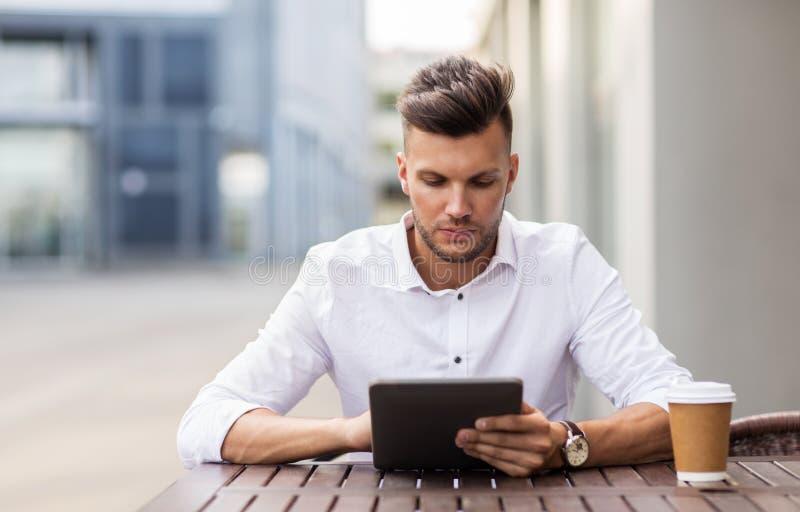 Hombre con PC y café de la tableta en el café de la ciudad fotografía de archivo