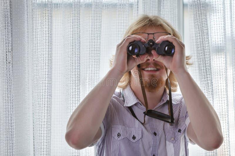 Hombre con prismáticos espiando a sus vecinos fotografía de archivo