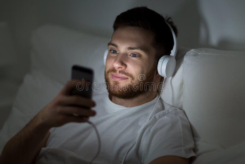 Hombre con smartphone y auriculares en cama en la noche fotografía de archivo