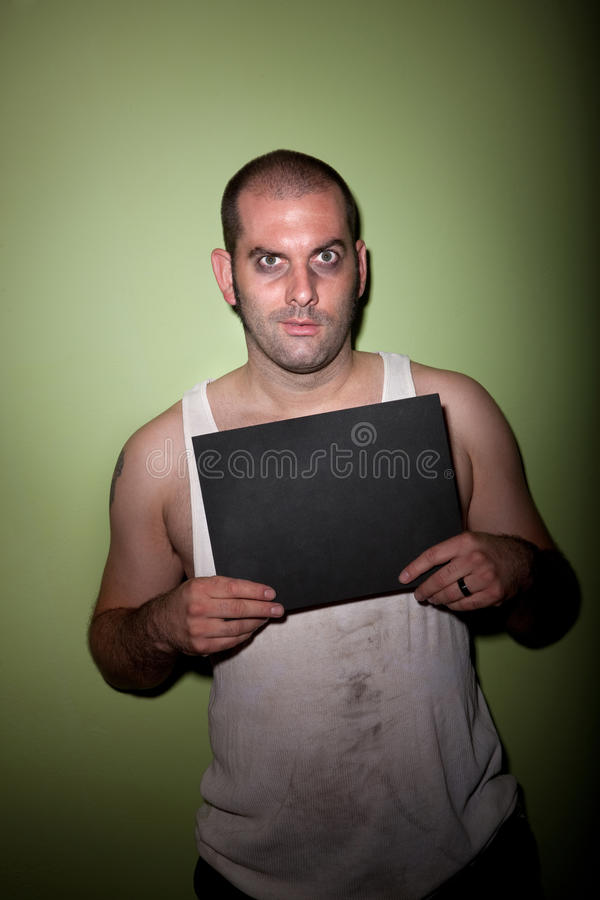Hombre con sonrisa torcida en mugshot imagen de archivo libre de regalías