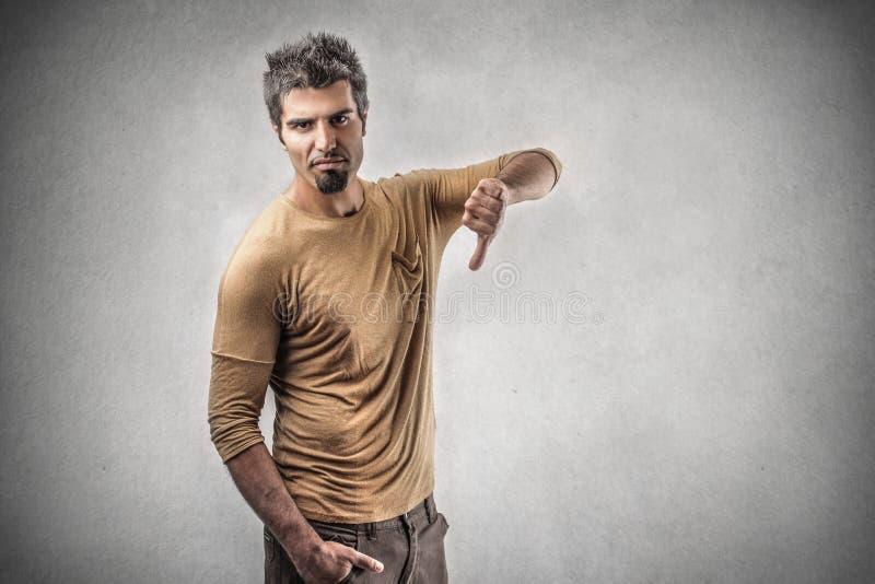 Hombre con su pulgar abajo imagen de archivo libre de regalías