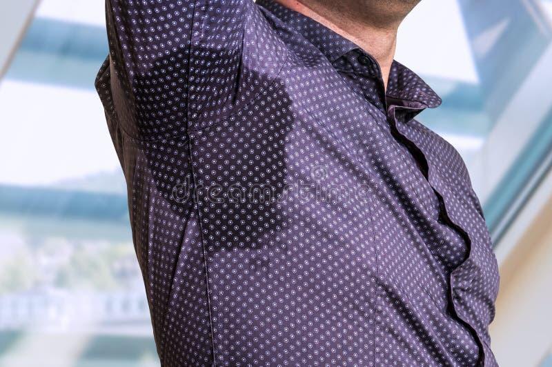Hombre con sudar debajo del axila en oficina de negocios fotografía de archivo