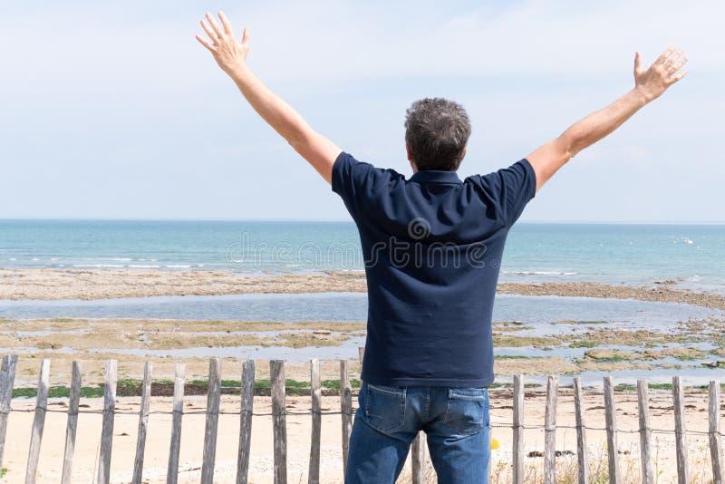 Hombre con sus brazos en el aire en vista posterior trasera en verano de la playa de Ile de re fotos de archivo libres de regalías