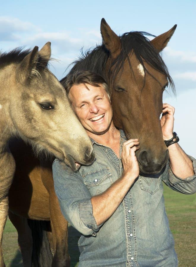 Hombre con sus caballos imagen de archivo