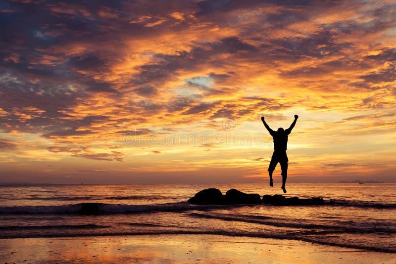 Hombre con sus manos para arriba en el tiempo de la puesta del sol imagen de archivo