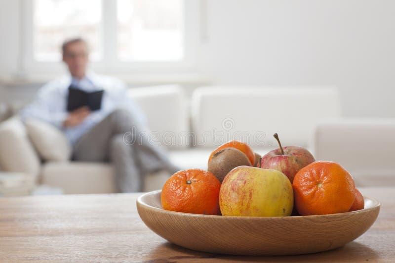 Hombre con tableta sentado en un salón con frutas en primer plano fotos de archivo libres de regalías