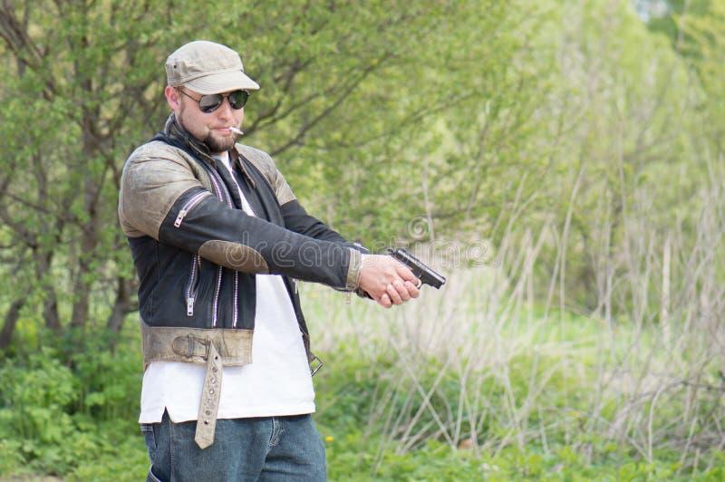 Hombre con un arma en el bosque imagenes de archivo