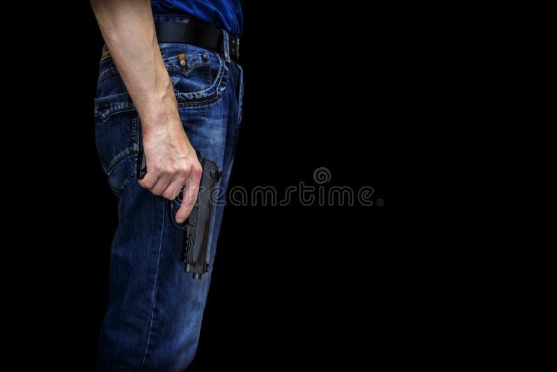 Hombre con un arma en su mano en un fondo negro imagen de archivo