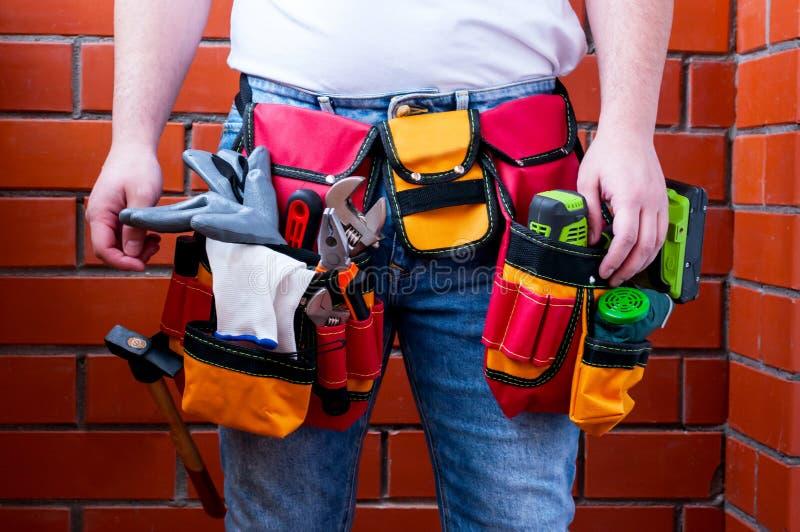 Hombre con un casco protector en su mano contra la perspectiva de una pared de ladrillo roja con la bolsa de herramientas del ton fotos de archivo libres de regalías