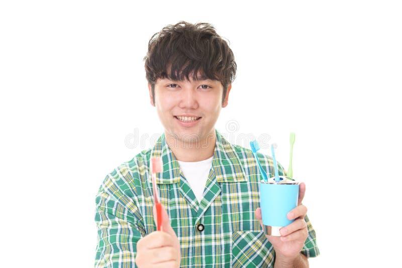 Hombre con un cepillo de dientes imagenes de archivo