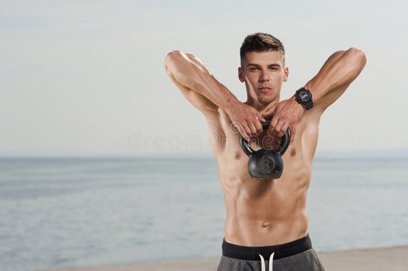 Hombre con un cuerpo desnudo que hace ejercicio del kettlebell imagenes de archivo