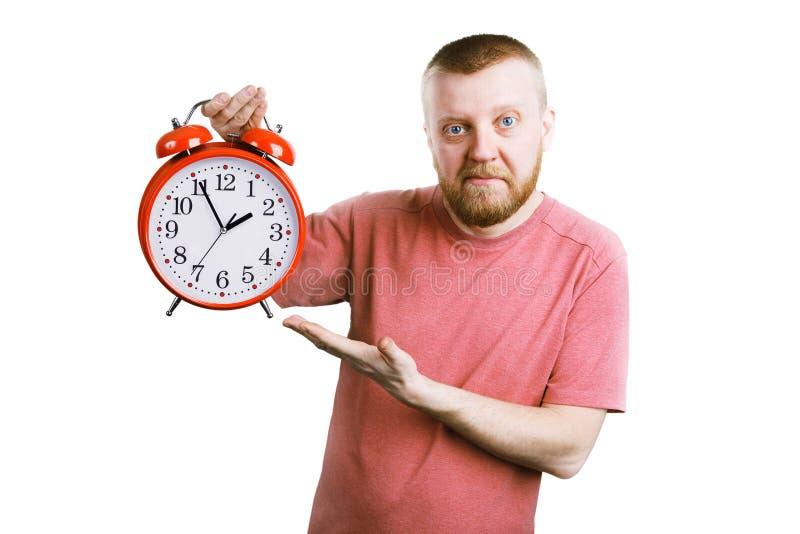 Hombre con un despertador rojo en su mano imágenes de archivo libres de regalías