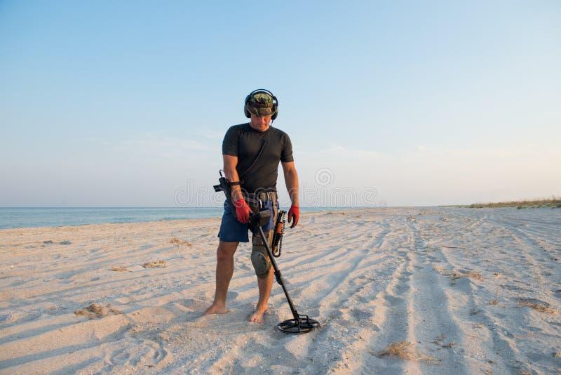 Hombre con un detector de metales en una playa arenosa del mar fotos de archivo libres de regalías