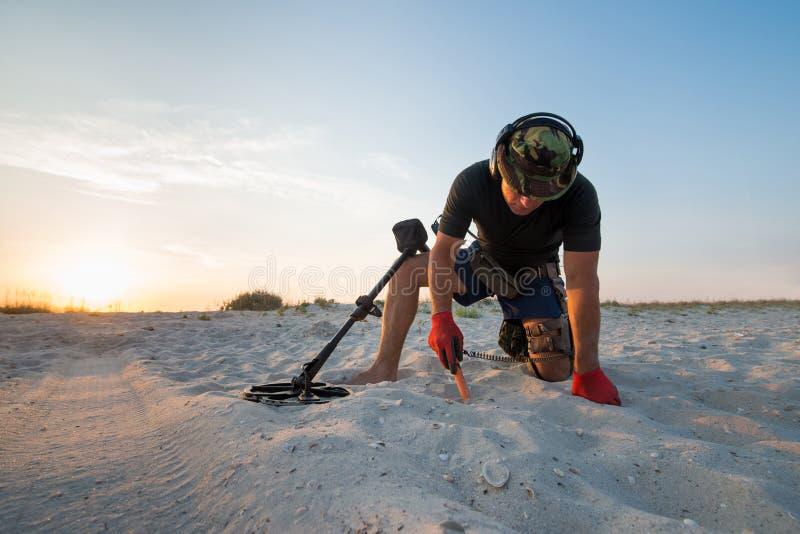 Hombre con un detector de metales en una playa arenosa del mar imagenes de archivo