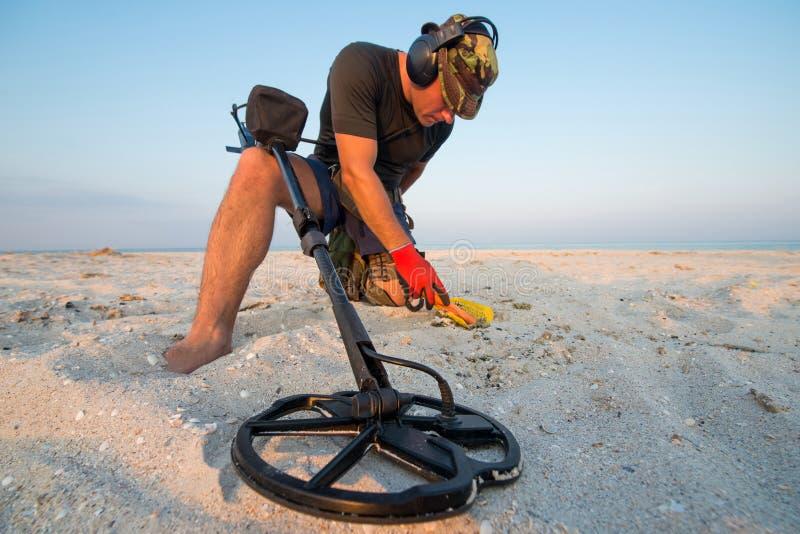 Hombre con un detector de metales en una playa arenosa del mar imágenes de archivo libres de regalías