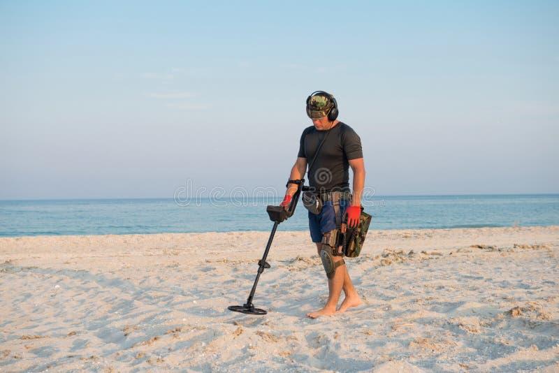 Hombre con un detector de metales en una playa arenosa del mar imagen de archivo