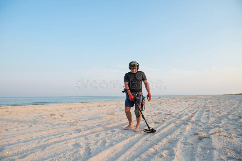 Hombre con un detector de metales en una playa arenosa del mar fotos de archivo