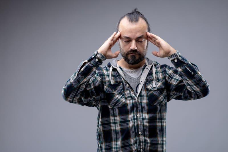 Hombre con un dolor de cabeza o concentrar imagen de archivo