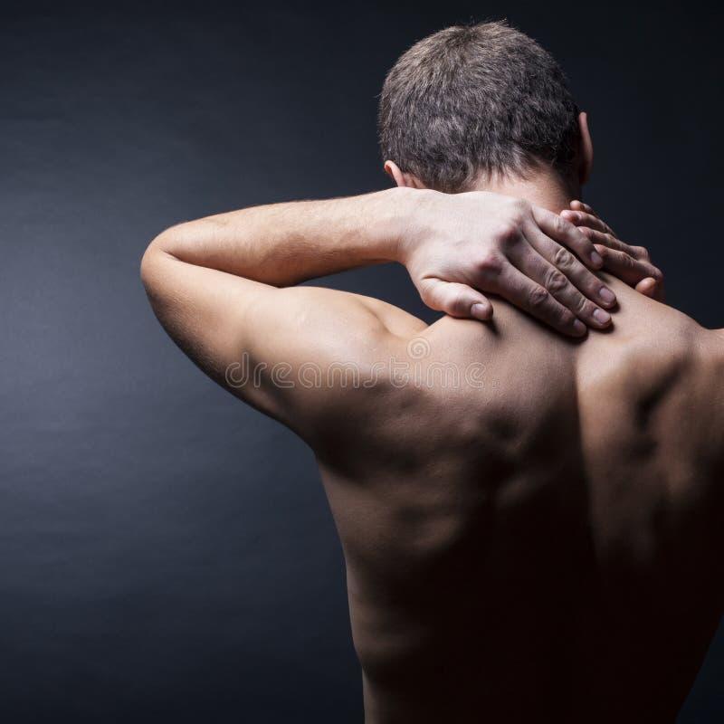 Hombre con un dolor en el cuello imagenes de archivo