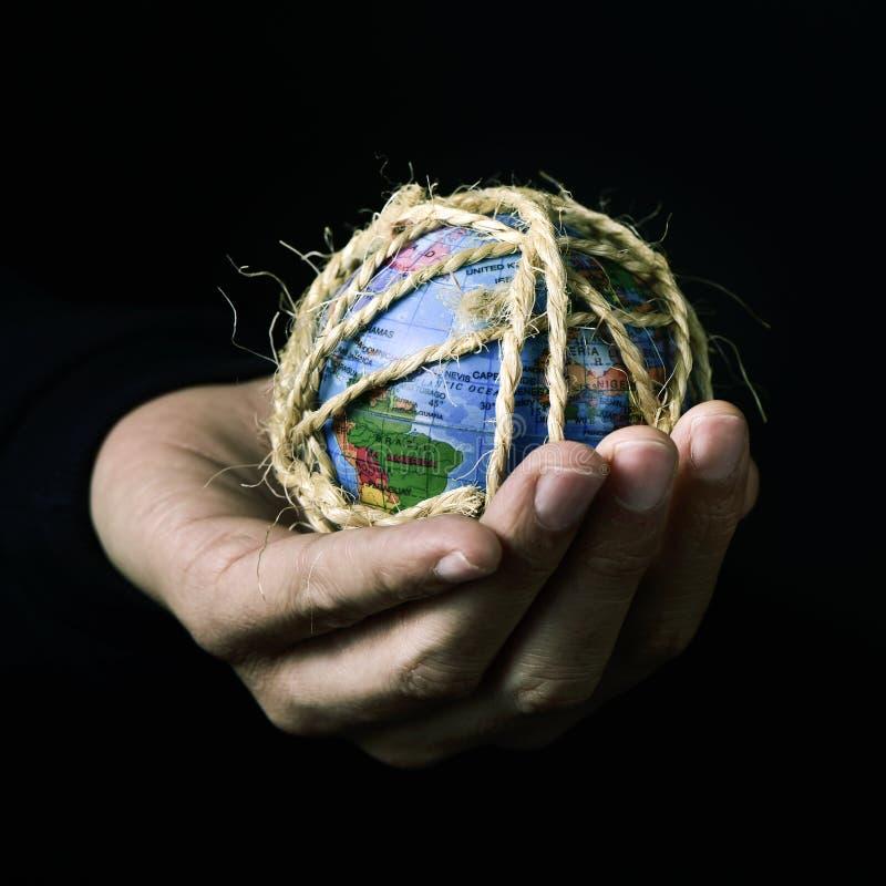 Hombre con un globo del mundo atado con la cuerda imágenes de archivo libres de regalías
