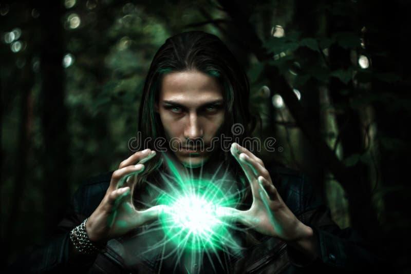 Hombre con un orbe que brilla intensamente misterioso fotografía de archivo libre de regalías