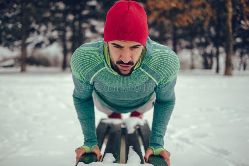 Hombre con un sombrero que hace pectorales en banco de parque en la nieve foto de archivo libre de regalías