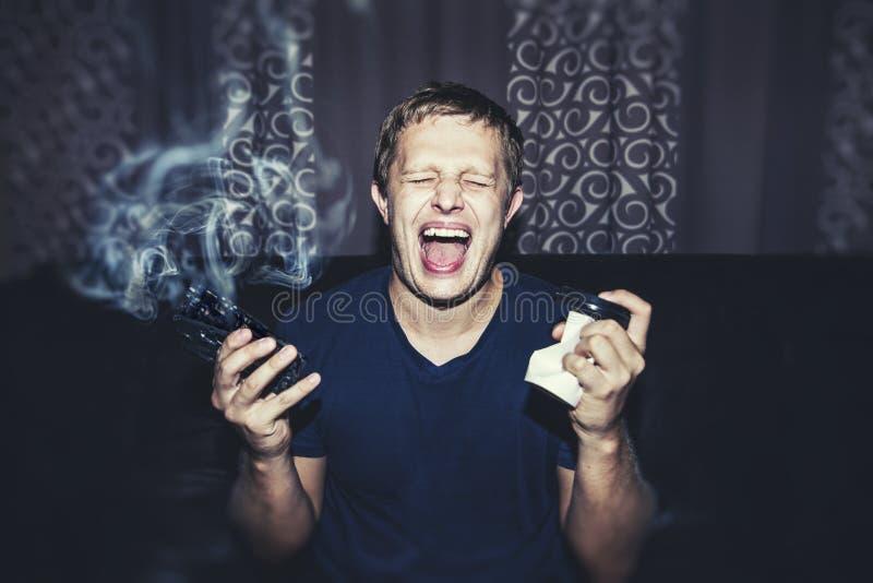 Hombre con un teléfono roto que fuma y una taza de café arrugada fotos de archivo