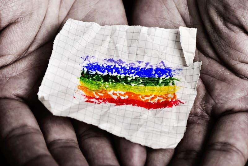 Hombre con un trozo de papel con una bandera del arco iris fotos de archivo libres de regalías