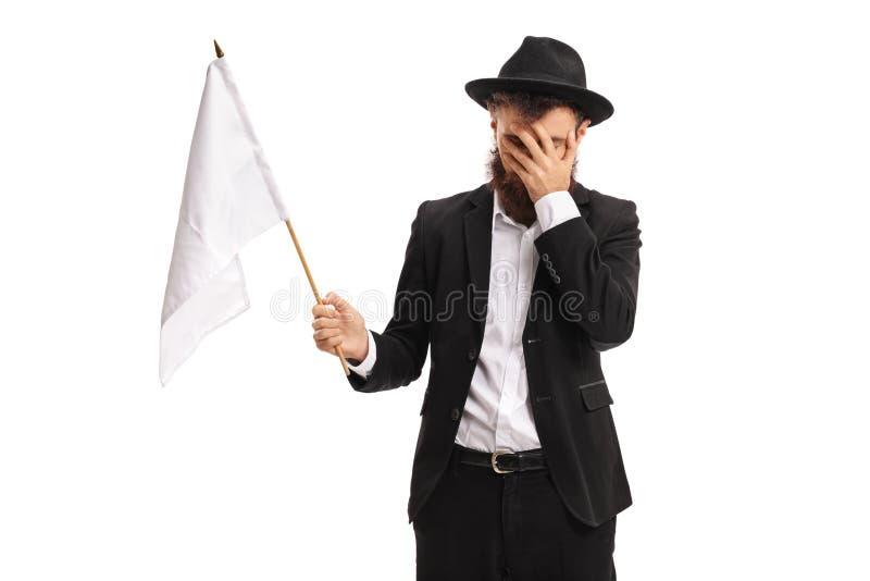 Hombre con una bandera blanca que lleva a cabo su cabeza con incredulidad imágenes de archivo libres de regalías