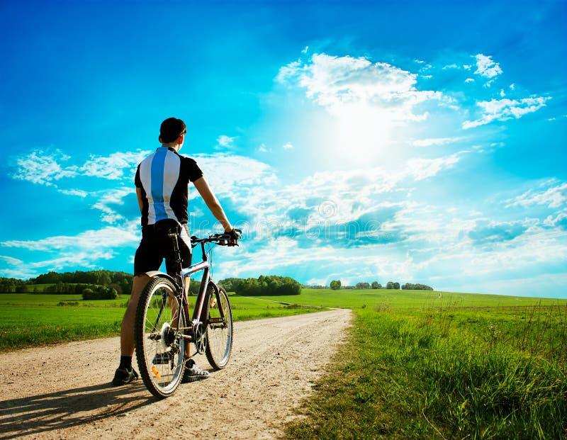 Hombre con una bici en fondo hermoso de la naturaleza fotografía de archivo libre de regalías
