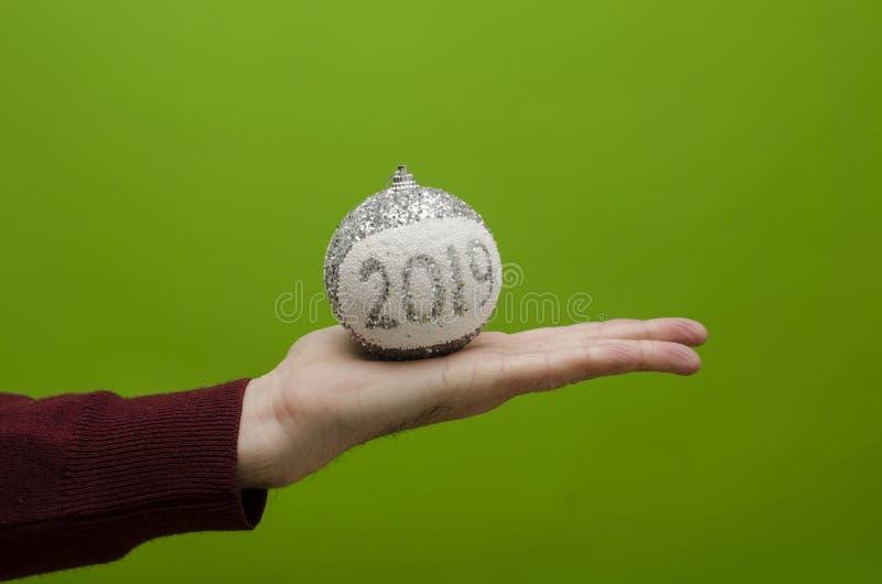 Hombre con una bola de la Navidad que indica el año feliz 2019 imagen de archivo