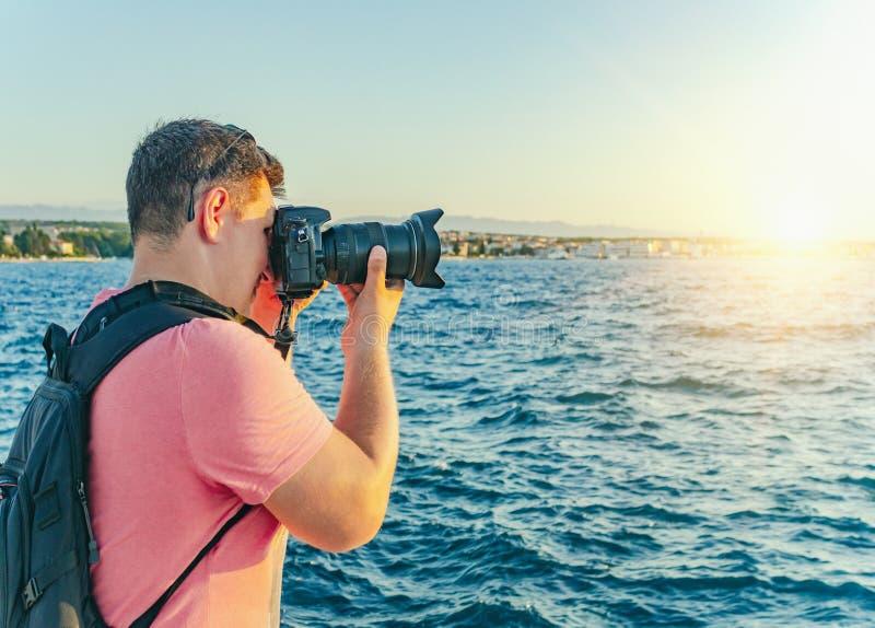 Hombre con una cámara que fotografía la puesta del sol en la costa de mar fotos de archivo