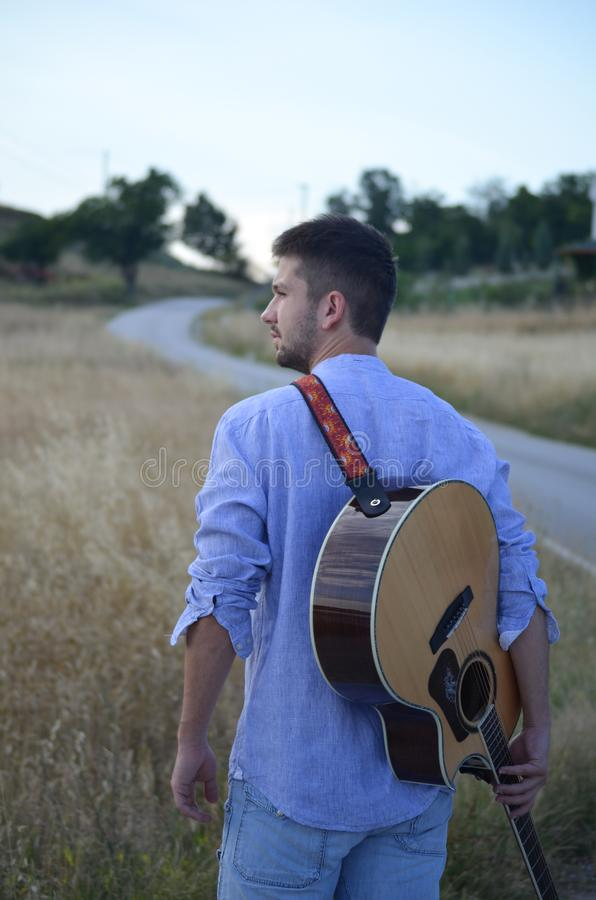 Hombre con una guitarra que cuelga la suya detr?s fotografía de archivo