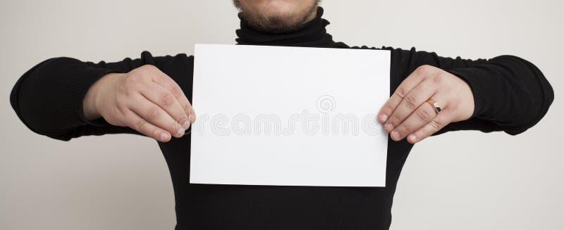 Hombre con una hoja de papel blanca imágenes de archivo libres de regalías