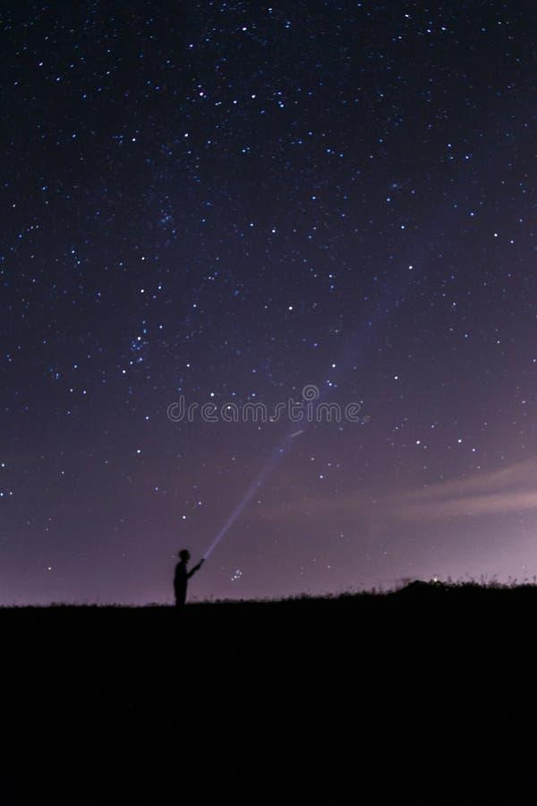 Hombre con una linterna debajo de un cielo nocturno estrellado stock de ilustración