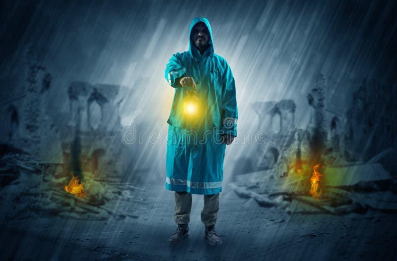 Hombre con una linterna que brilla intensamente en una escena de la catástrofe fotografía de archivo