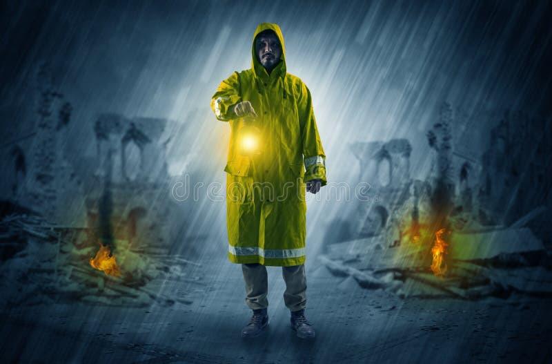 Hombre con una linterna que brilla intensamente en una escena de la catástrofe imagen de archivo