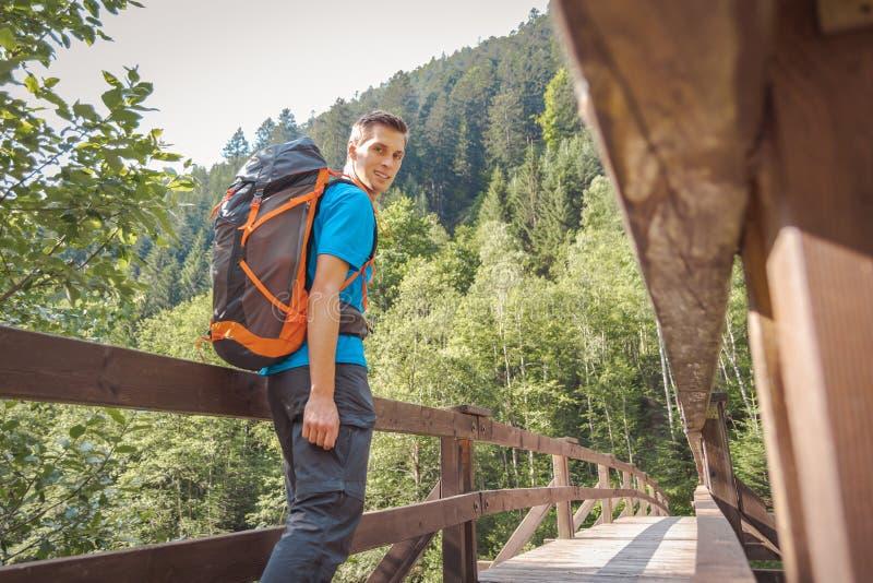 Hombre con una mochila que camina en un puente en el bosque imagen de archivo libre de regalías