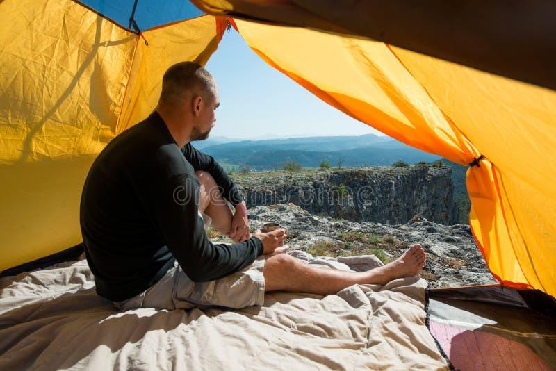 Hombre con una taza en acampar al aire libre imagen de archivo