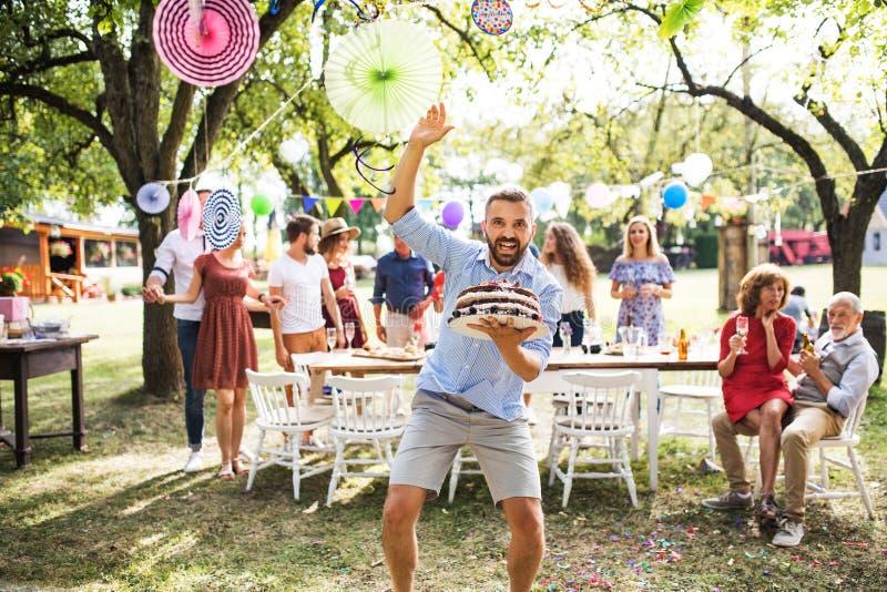 Hombre con una torta en una celebración de familia o una fiesta de jardín afuera imagenes de archivo
