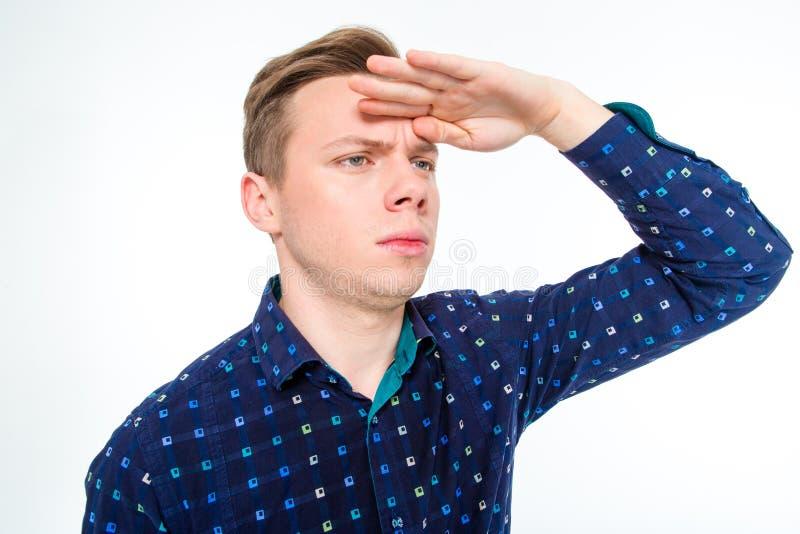 Hombre concentrado de diversión que mira lejos con los ojos antedichos de la mano fotos de archivo libres de regalías