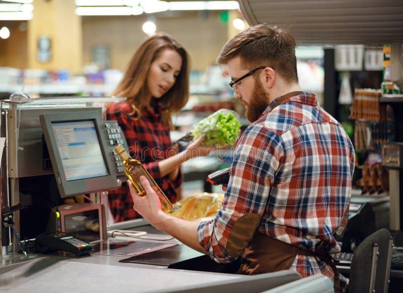 Hombre concentrado del cajero en espacio de trabajo en tienda del supermercado fotografía de archivo